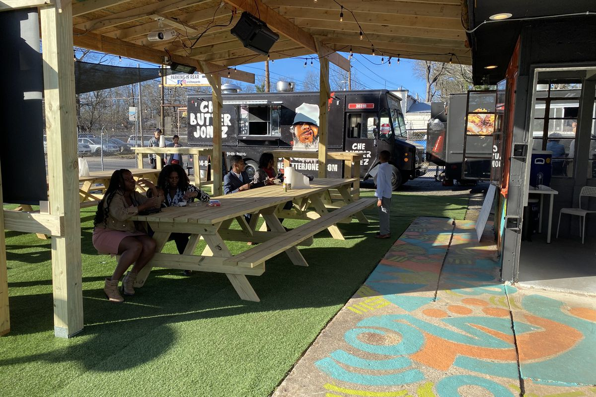 Two women sitting on a covered patio at a picnic table eating at the Triton Yards food truck park with Che Butta Food Truck parked in the background