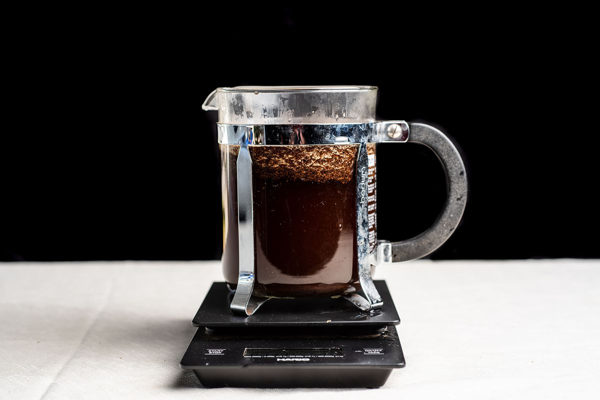 A short French press sitting on top of a digital scale.