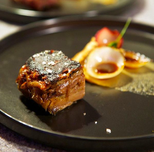 A chunk of cooked meat dusted with glittery sauce on a plate beside other avant-garde ingredients blurred in the background