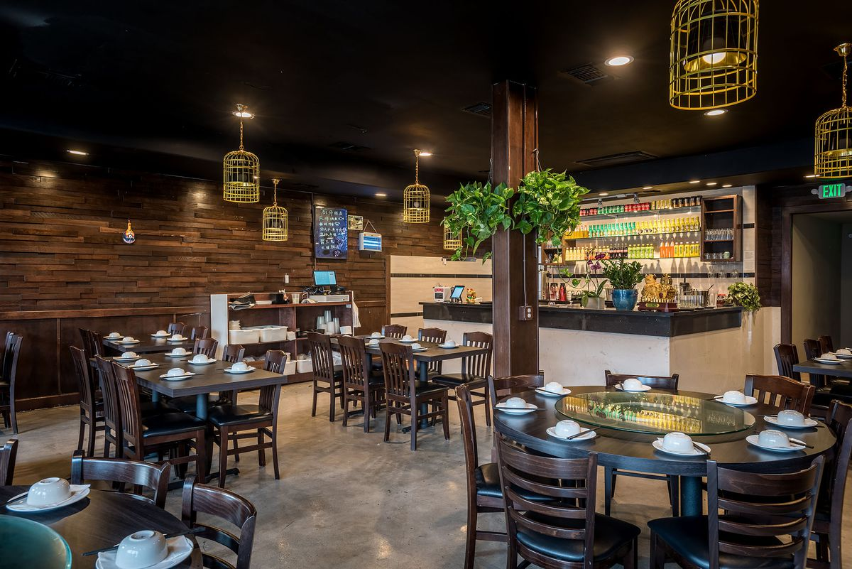 Inside a Chinese restaurant with hanging plants and circular wooden tables.