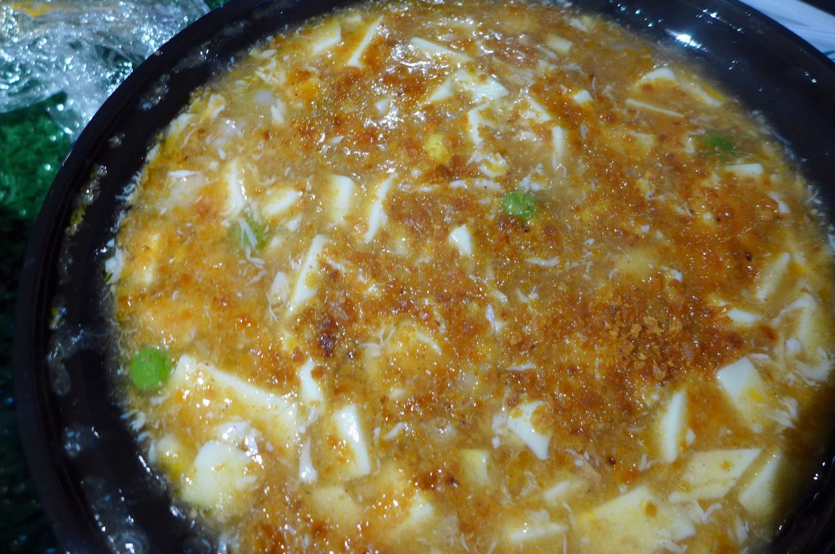 A bright and murky stew bobbing shards of tofu in an orangeish soup.