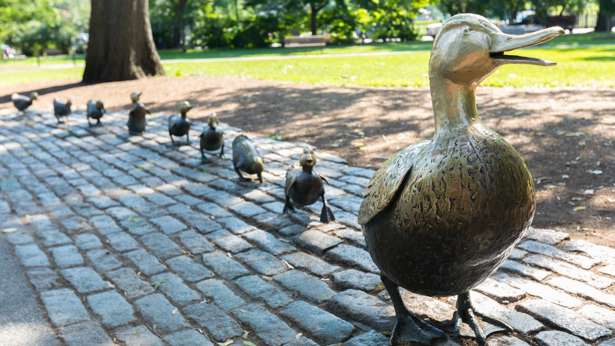 Small bronze sculptures of a mother duck with her ducklings in tow.