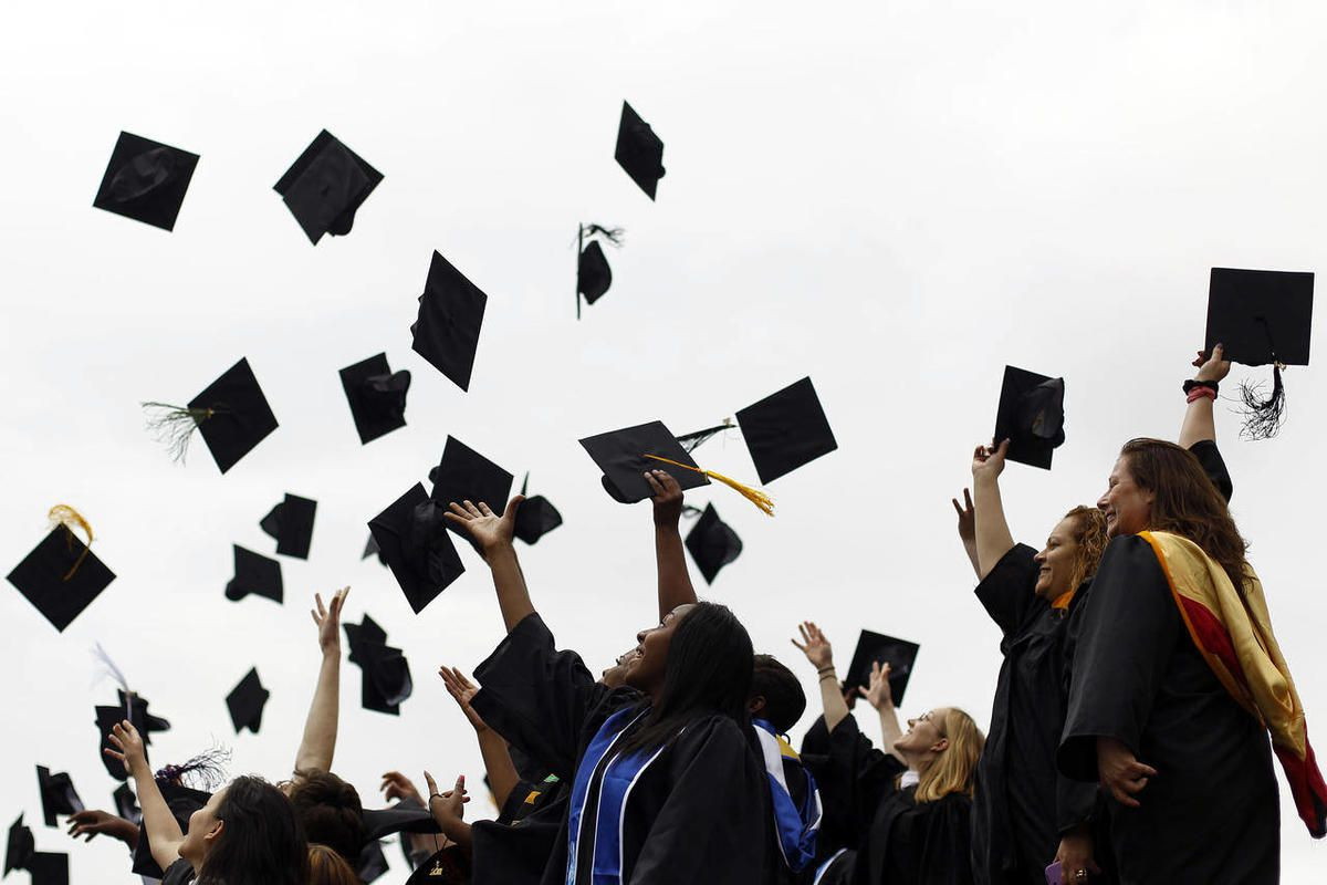 FILE-In this May 20, 2011, file photo, graduates from various institutions toss their hats in the air in Philadelphia. Many graduatues are burried in student loans, but Joe Mihalic, a  business school graduate paid off $90k in student loans in 7 months an
