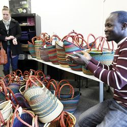 Doctor Abio Ayeliya, right, sells baskets from his home village in Ghana during a volunteer open house event at the Utah Refugee Education and Training Center in Salt Lake City, Saturday, Jan. 9, 2016. Abio Ayeliya uses the profits for a foundation in his home country.
