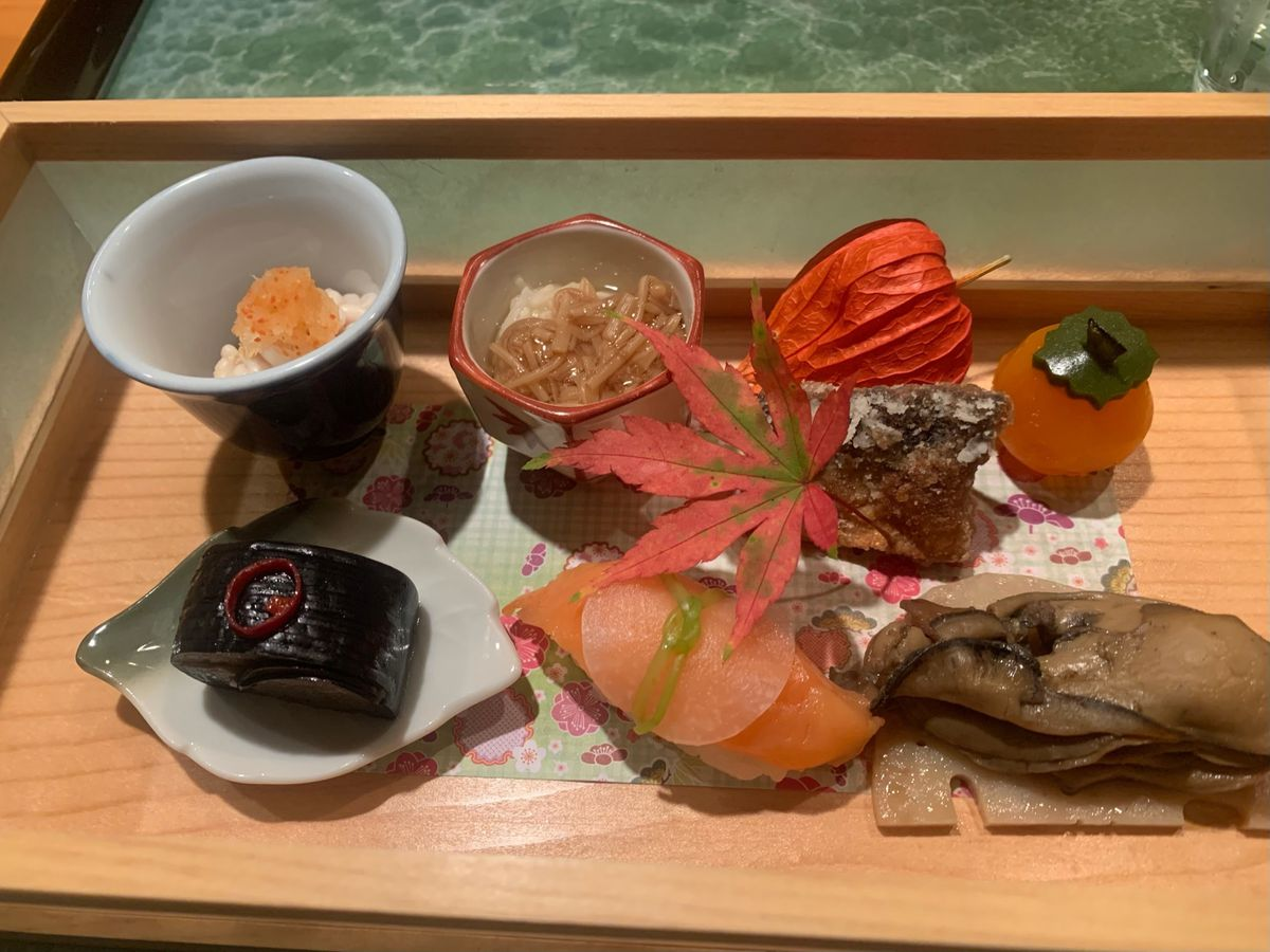 A spread of seasonal appetizers on a wooden tray, with a red leaf indicating the autumn season