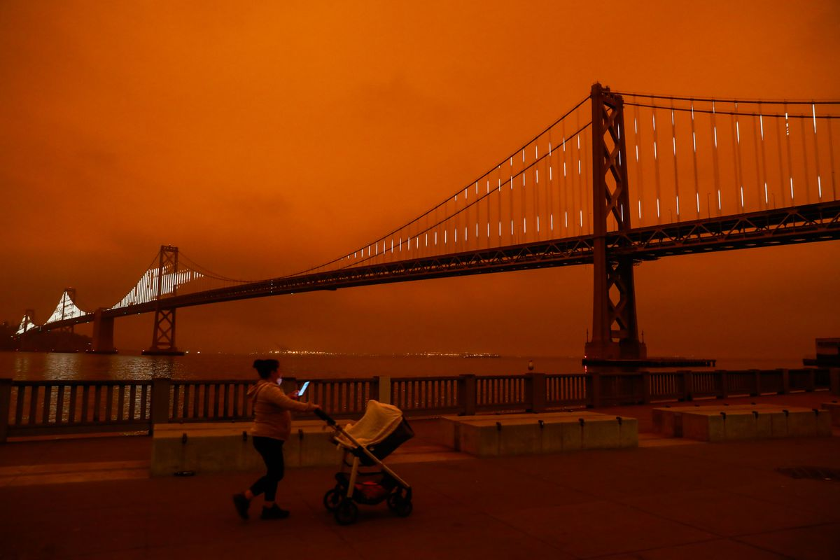 A person pushes a stroller along the waterfront in San Francisco with the  Bay Bridge and an orange sky behind them.