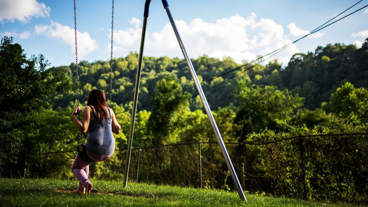 A child sitting on a swing set.