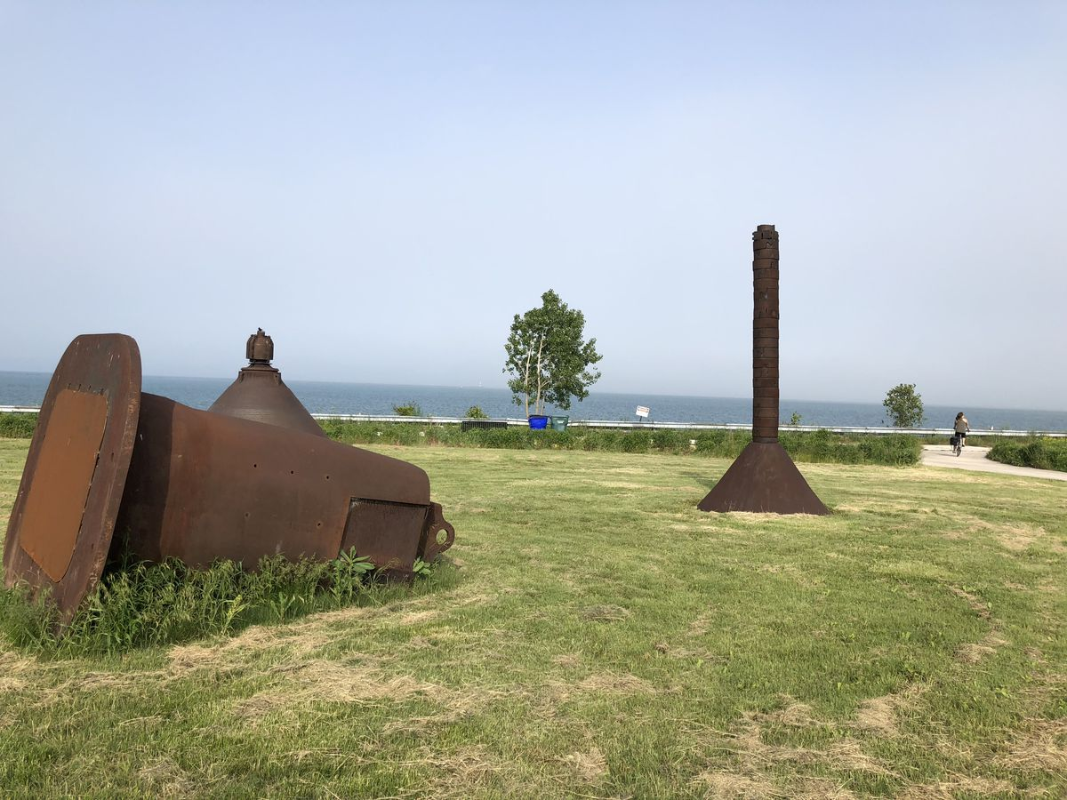 An image of rusted steel sculptures in a grassy park near the lakefront with water and blue sky in the background.