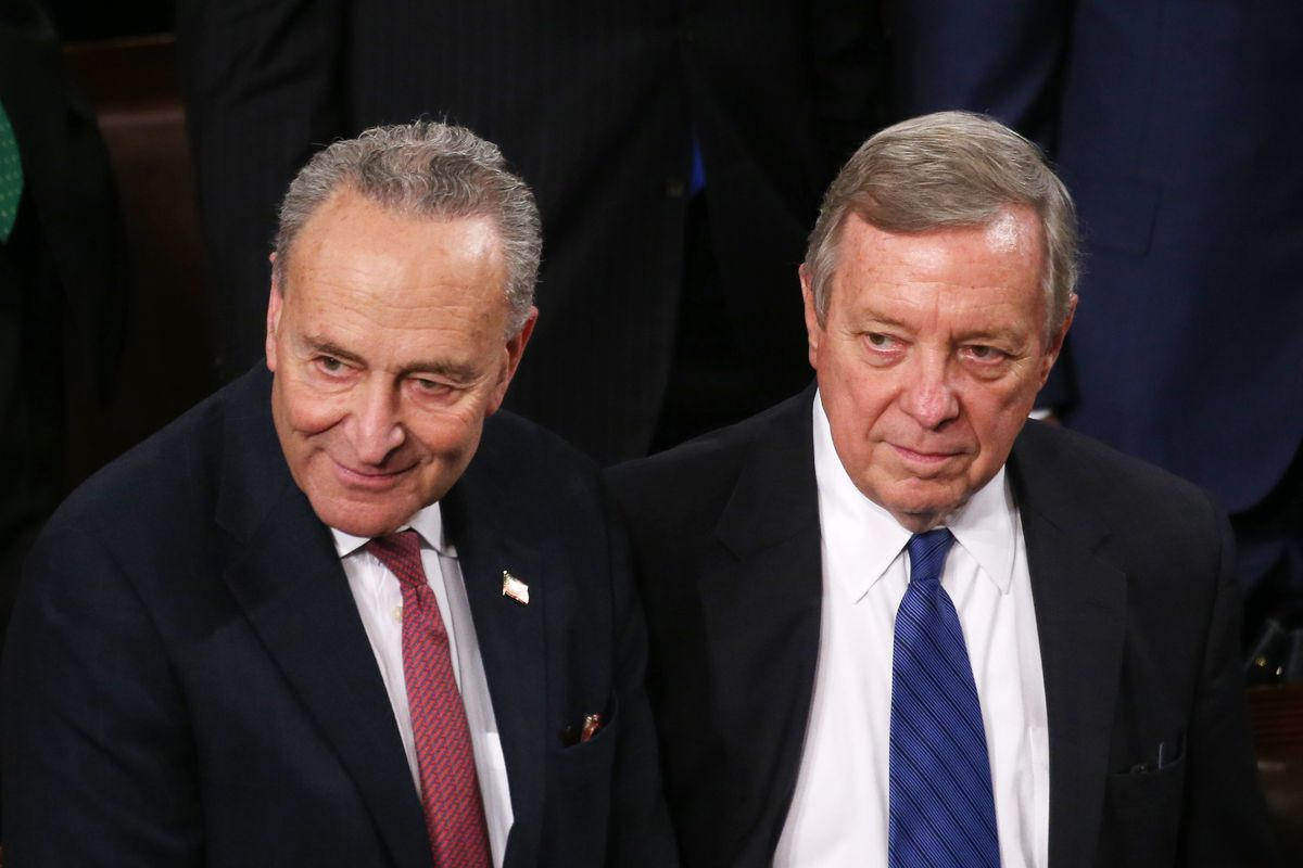 Schumer, to the left of Durbin, smiles slightly, while Durbin wears a serious expression. Both men have on dark suits; Schumer, without his glasses in this photo, wears a red tie; Durbin has on a blue tie. Behind them, the blue carpet of the House of Representatives is visible.