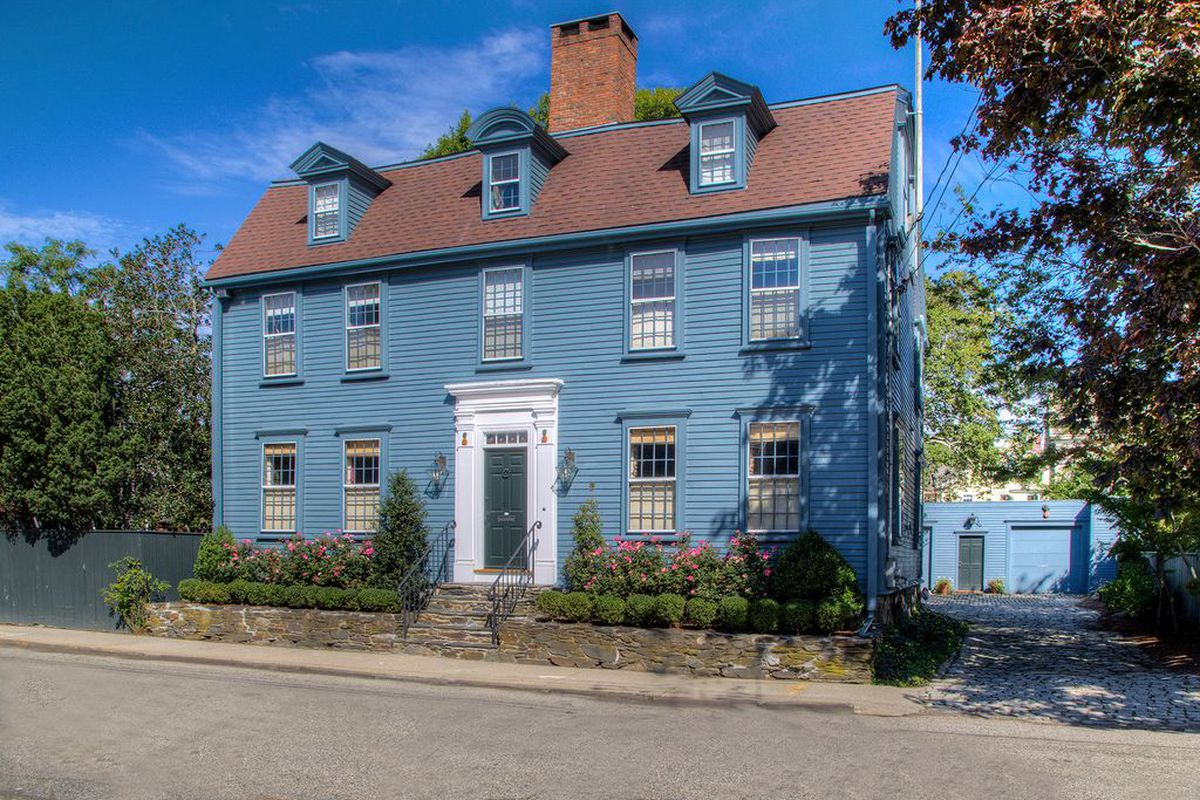 Exterior shot of dusty-blue-painted wood Colonial with white entrance and three dormer windows set right against the street.