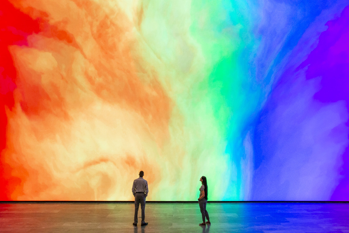 Two people standing in front of massive screen showing swirls of rainbow colors.
