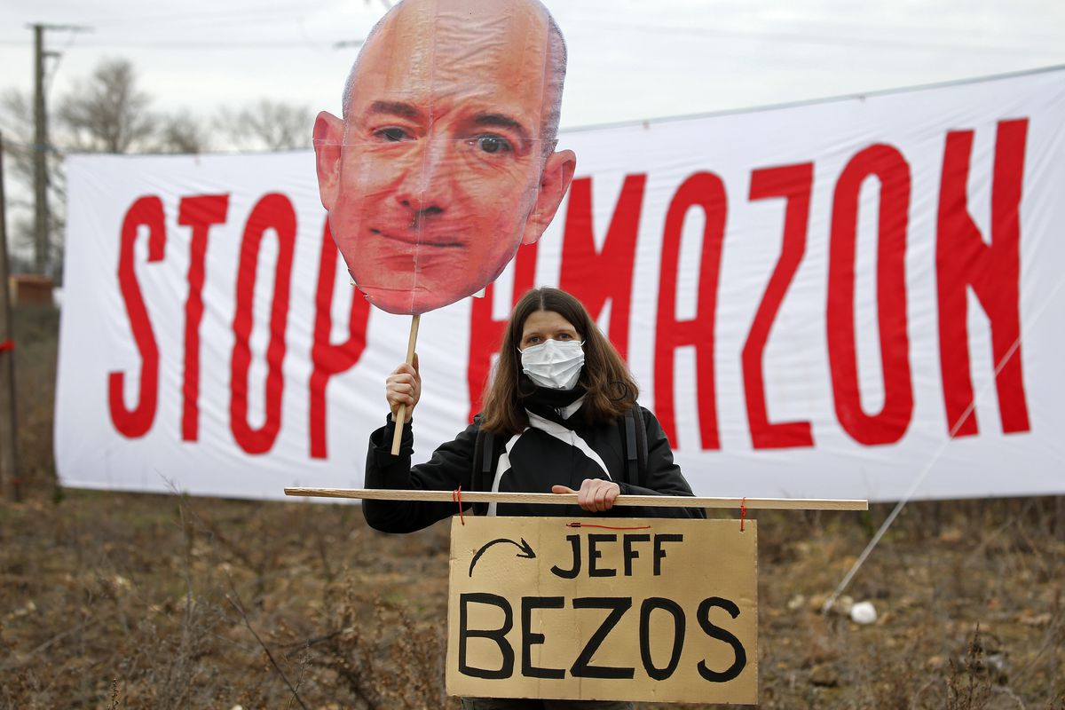 """A protester holds up a large cutout of Jeff Bezos's face while standing in front of a sign that reads """"stop Amazon."""""""