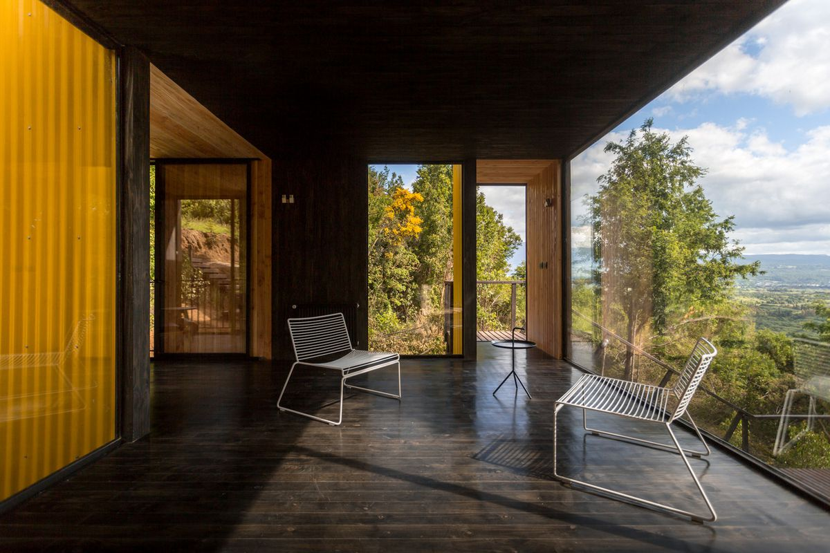 Two chairs next to large windows