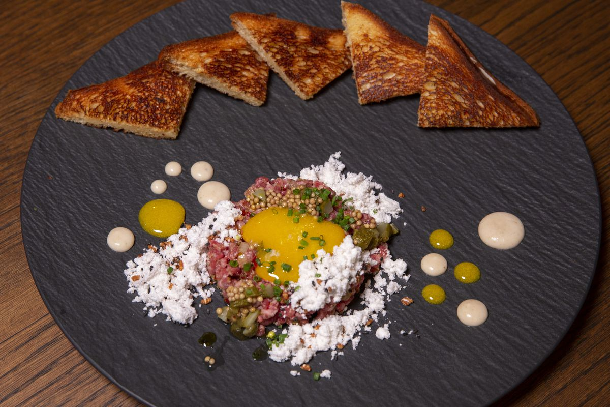A round plate with colorful raw beef with an egg yolk in the middle and toast points.