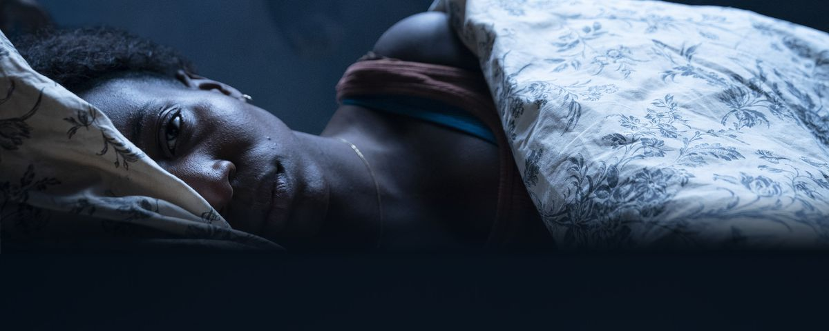 A Black woman lies in bed awake while a horse looms behind her in Kindred