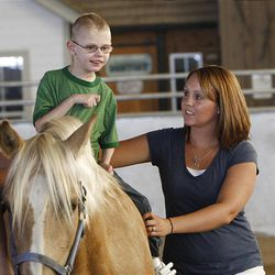 Deacon Nielson, 5, who had a severe stroke when he was 4 months old, rides Summer with the help of Andrea Smith at the Buffalo Ranch in Farmington on Thursday. The therapeutic riding is organized by the nonprofit group Therapeutic Assets.