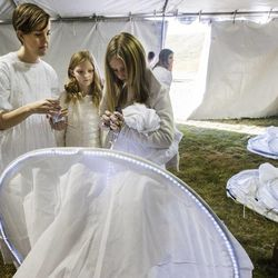Dana Ohlsen, Dylann Riggs and Maya Riggs work to get a costume ready as More than 1,000 participants gather Monday, Dec. 1, 2014, at Rock Canyon Park in Provo to set a world record for the largest live Nativity.