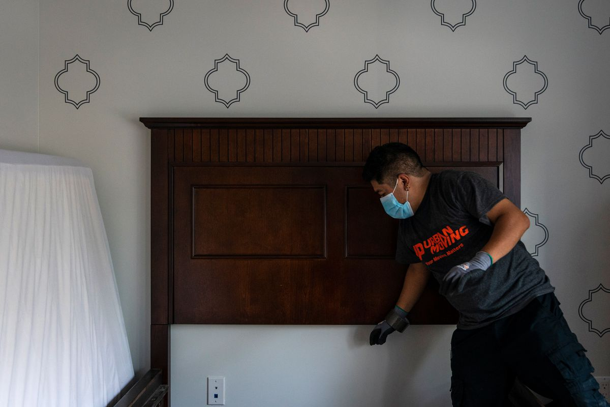 Alfredo Plaza disassembles a bed in the master bedroom during a move from a Bed-Stuy, Brooklyn apartment, Aug.14, 2020.