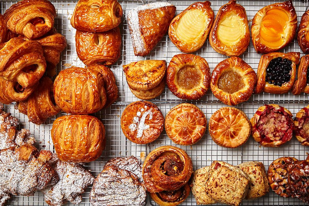 A top-down view of croissants, tarts, and other pastries on a baking sheet.