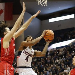 UConn's Jalen Adams (4) tries to avoid a Boston University defender as he goes to the basket.
