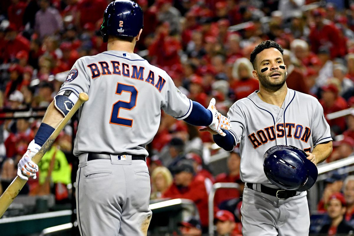 Houston Astros second baseman Jose Altuve celebrates with shortstop Alex Bregman after scoring during the fifth inning against the Washington Nationals in game three of the 2019 World Series at Nationals Park.