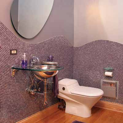 Two toned purple bathroom with small square shaped tiles on the walls and an oval shaped mirror.