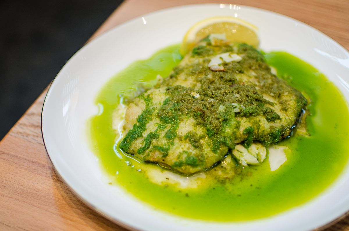 A white filet of fish sits in a pool of greenish oil, covered with green herbs and sliced garlic, with a lemon slice on the side.
