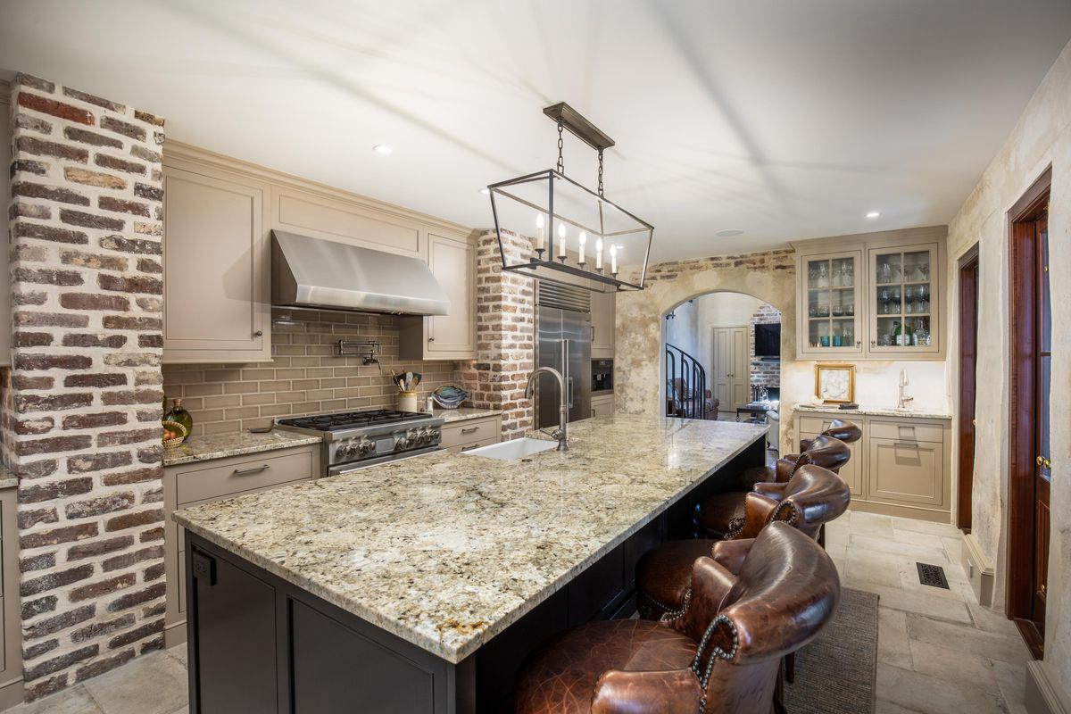 A kitchen has a large granite counter with leather bar stools.