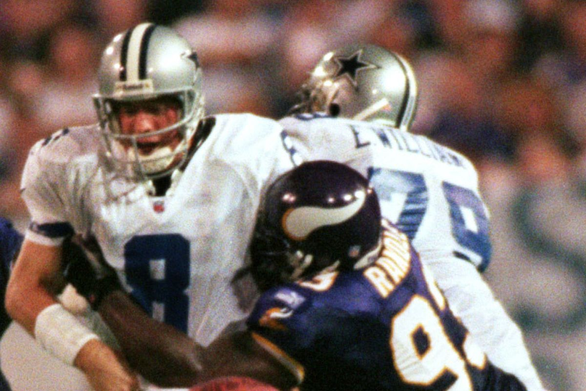 Dallas vs Vikings at Metrodome — Dallas quarterback Troy Aikman grimaces as he gets hit by Viking defensive tackle John Randle, loosing the ball, during a Monday night game at the Metrodome.