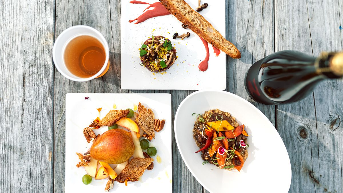A wooden table holds three plates containing a deep purple bison tartare, a dark rabbit stir fry over oats with colorful peppers, and a whole Magness pear surrounded by other fruits and cheeses.