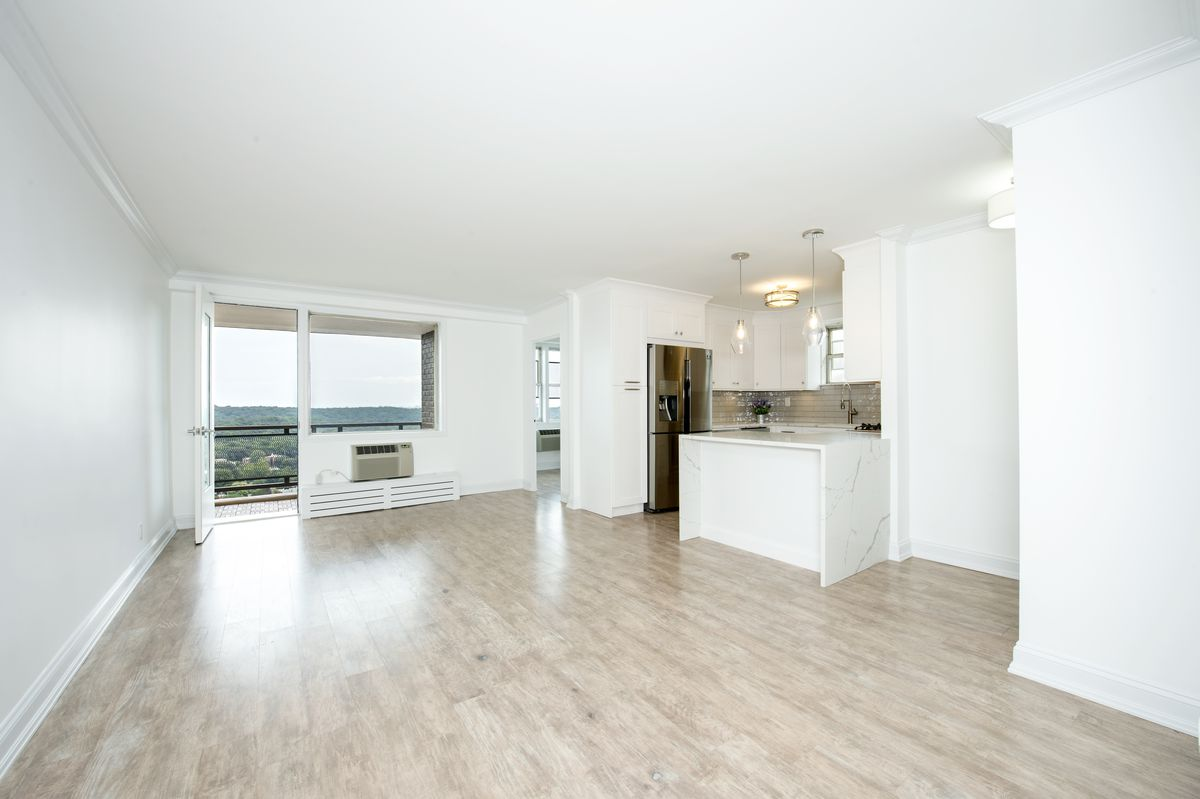 A living area with a door that leads to a terrace, hardwood floors, and white walls.