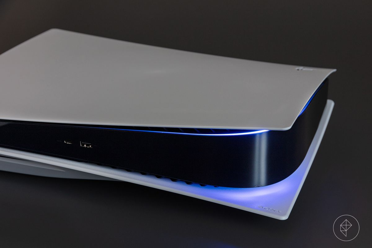 The PlayStation 5 laying on its side, turned on, showing a blue light at its edges