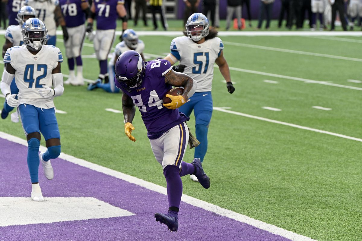Irv Smith Jr. #84 of the Minnesota Vikings runs past Jayron Kearse #42 and Jahlani Tavai #51 of the Detroit Lions to score a touchdown in the third quarter at U.S. Bank Stadium on November 08, 2020 in Minneapolis, Minnesota.