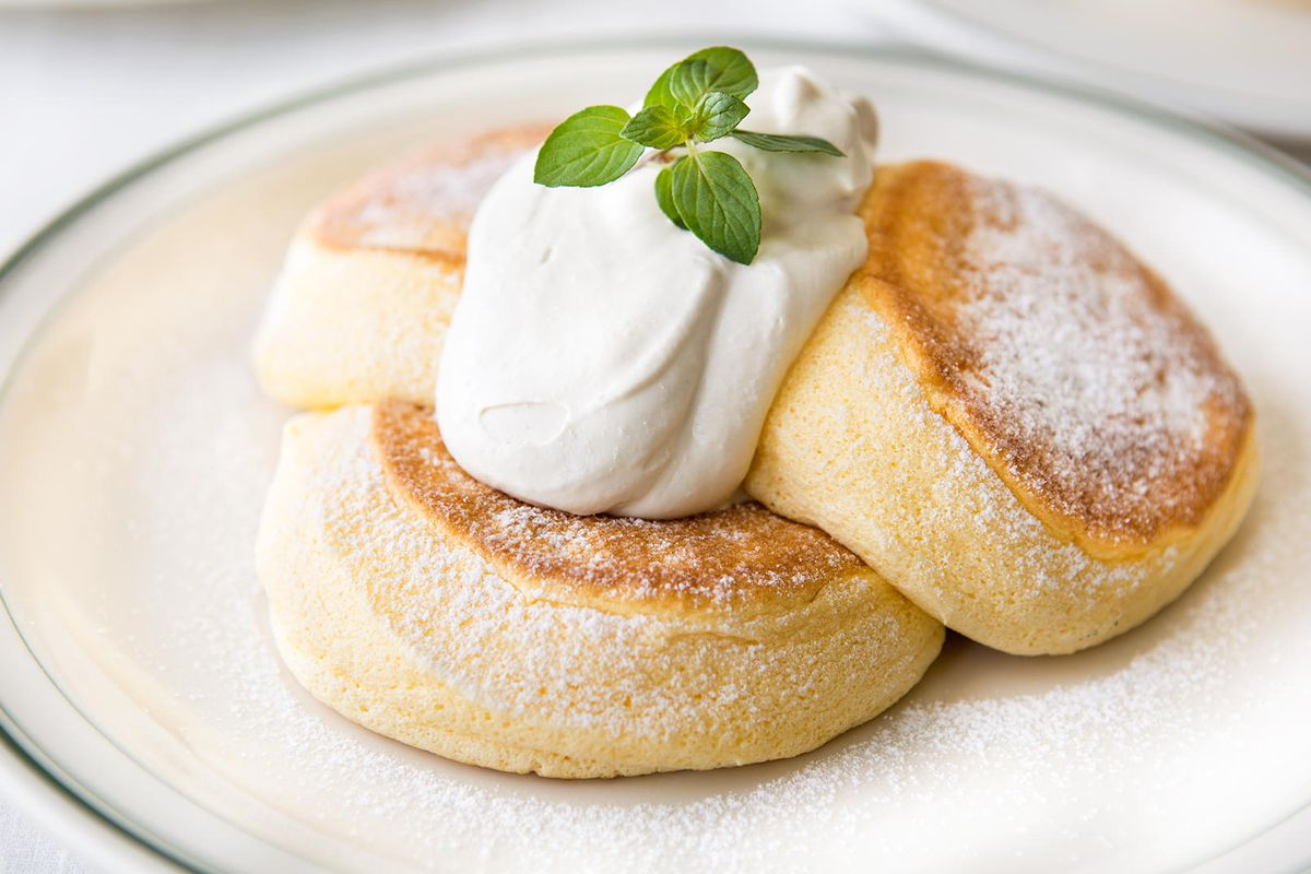 Three fluffy souffle pancakes on a plate with a dollop of whipped cream