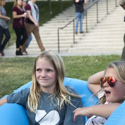 """Annie Oliver, 9, and Elle Pederson, 10, both of Orem, listen to their brothers' band """"Tommy and the Hunter"""" as the doors open to the LoveLoud Festival at Utah Valley University on Saturday, Aug. 26, 2017, in Orem. The festival was created by Dan Reynolds, lead singer of Imagine Dragons, to promote acceptance and support to individuals in the LGBTQ community. In addition, the festival sheds light on suicide prevalence in the LGBTQ community. LGBTQ inclusive groups such as The Trevor Project, GLAAD, Encircle and Stand4Kind benefited from the LoveLoud Festival."""