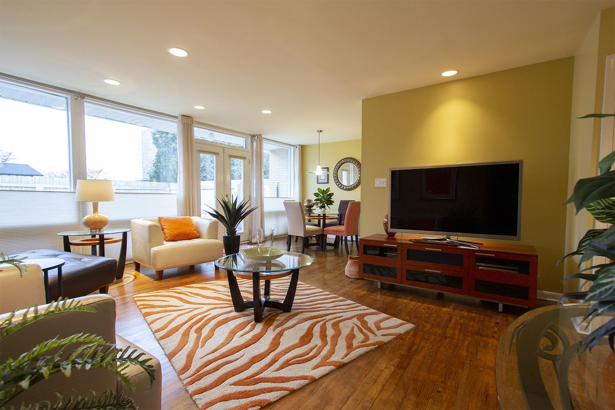 A room with orange leopard carpet and some leather sofas and chars facing a flat-screen TV.
