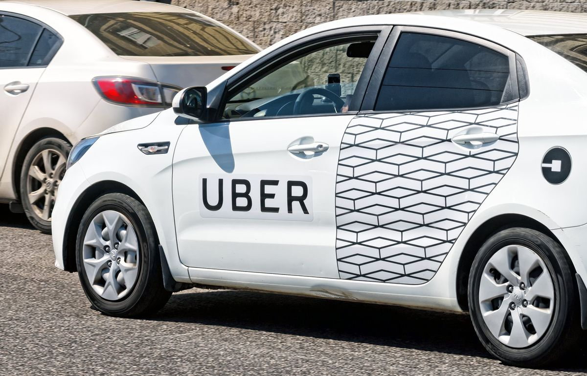 A white car with an Uber logo painted on the side in Moscow.