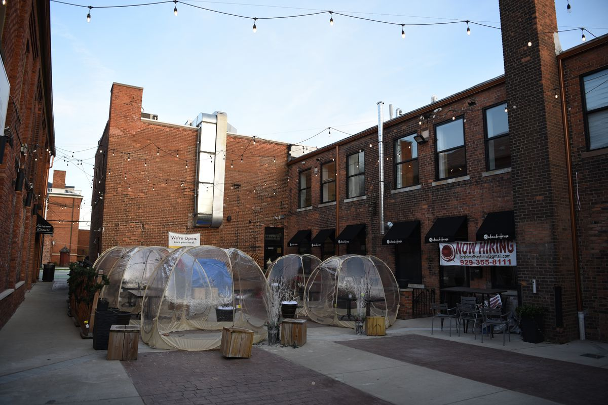 Five plastic tent domes sit on the back courtyard patio outside of Qahwah House in Dearborn.
