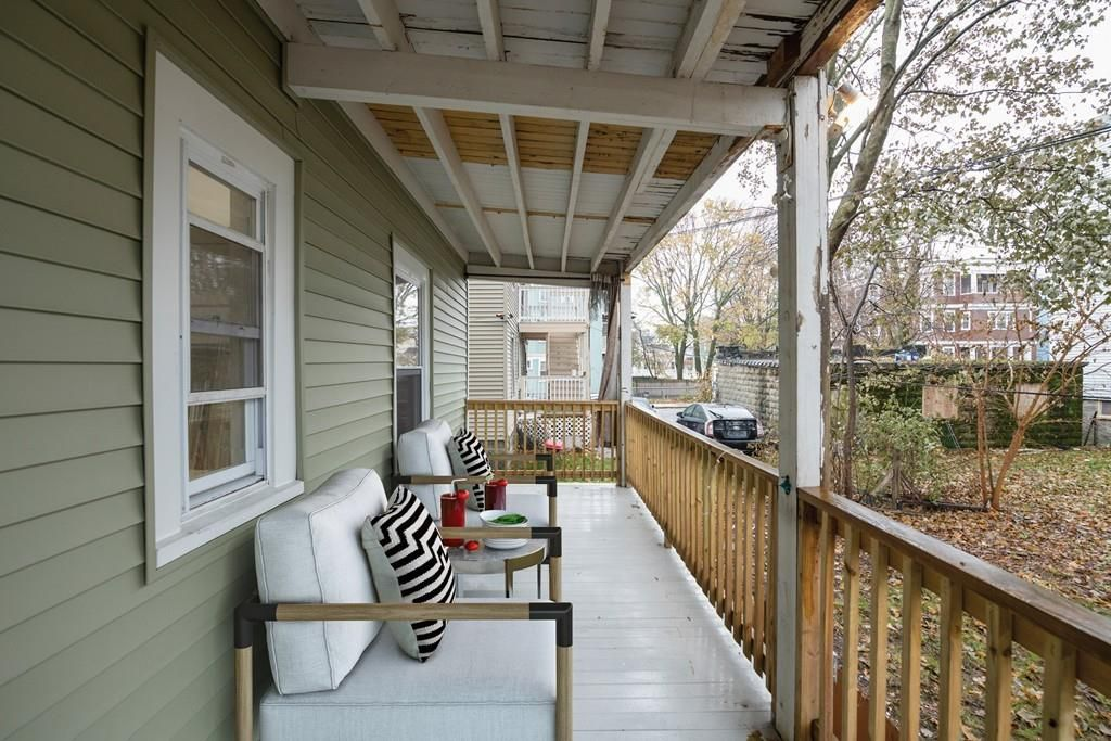 A long, narrow, wooden porch with two chairs facing out.