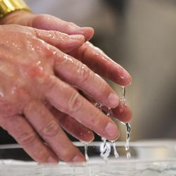 Water drips off Brian Horrocks' hands as his hands are blessed at the World Spiritual Health Organization combined board certification and chaplain graduation ceremony at the William E. Christofferson, Salt Lake Veterans Home on Wednesday, Aug. 2, 2017.
