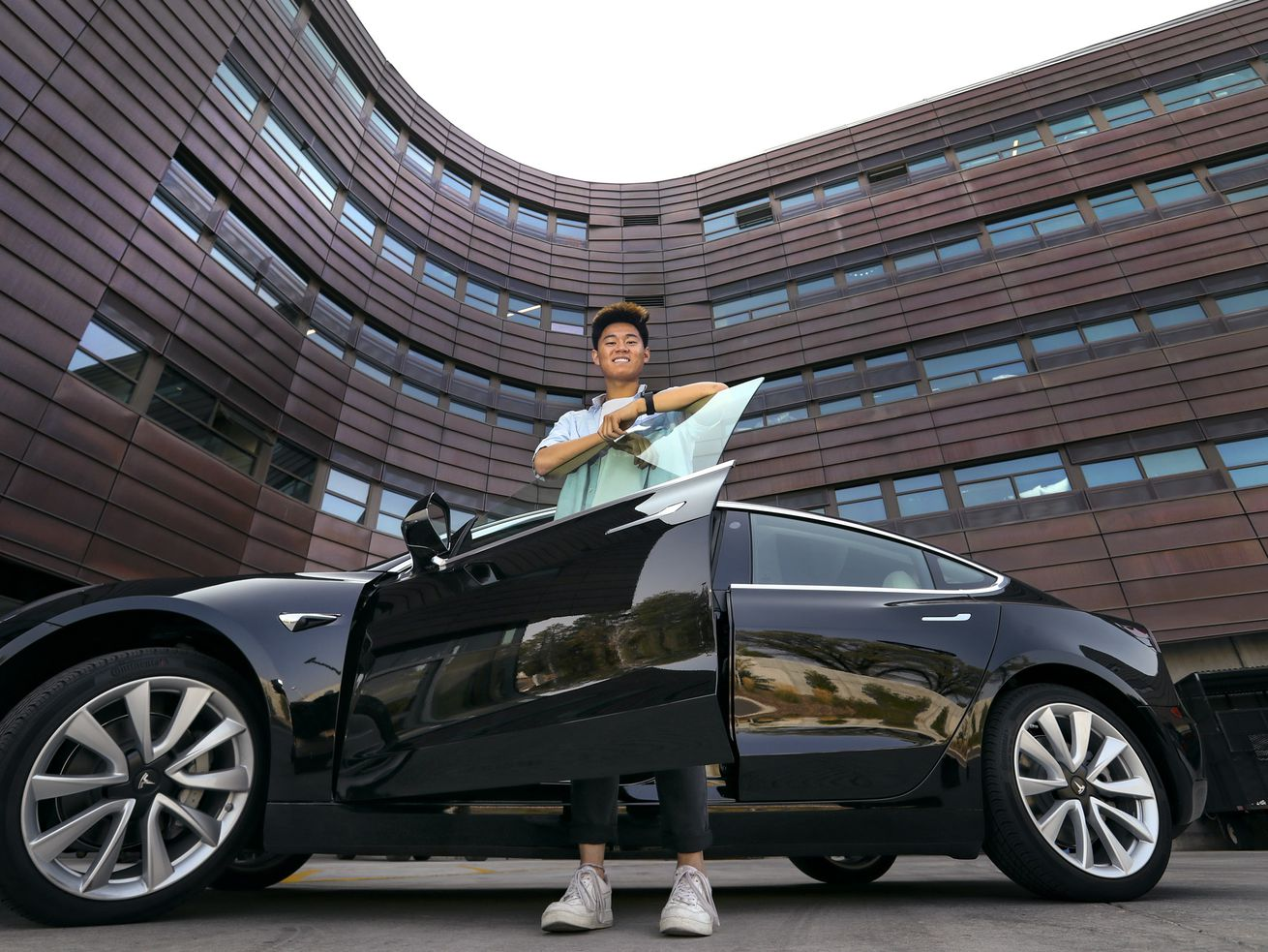 University of Utah freshman and game developer Andrew Wang poses for a photo with his Tesla Model 3 outside the Lassonde Entrepreneur Institute Studio building on the University of Utah campus in Salt Lake City on Tuesday, Oct. 6, 2020.