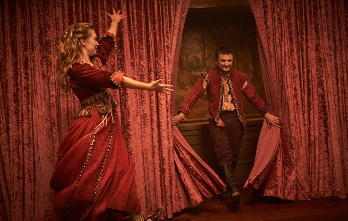 Mia Wasikowska, in an elaborate red jacket and skirt, presents Damon Herriman, also in red, as he emerges from a set of red velvet curtains.