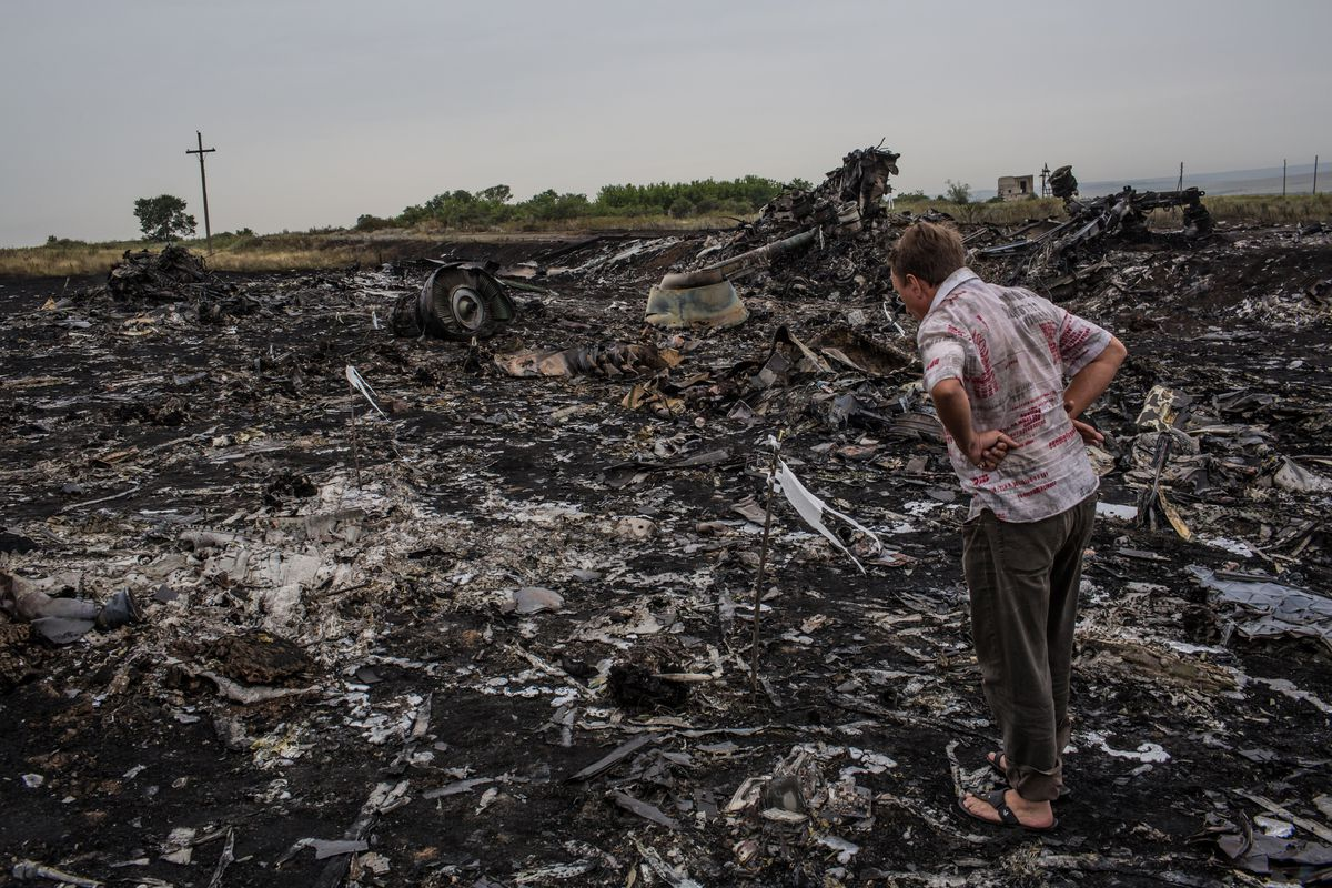 A local looks over the wreckage of MH17 in eastern Ukraine