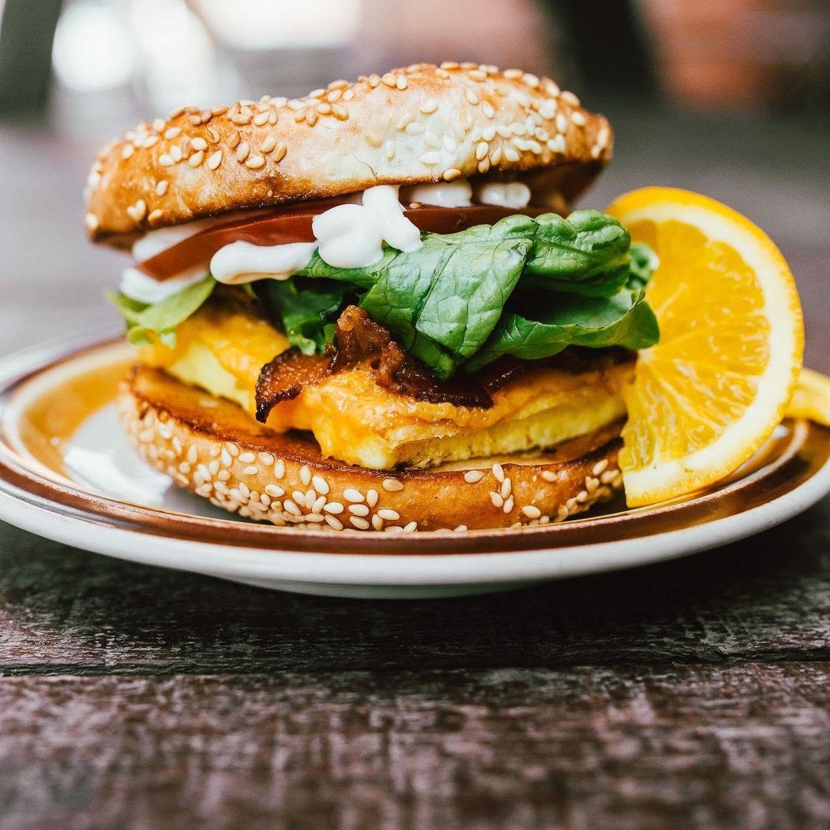 A bagel with breakfast sandwich fillings on a plate.