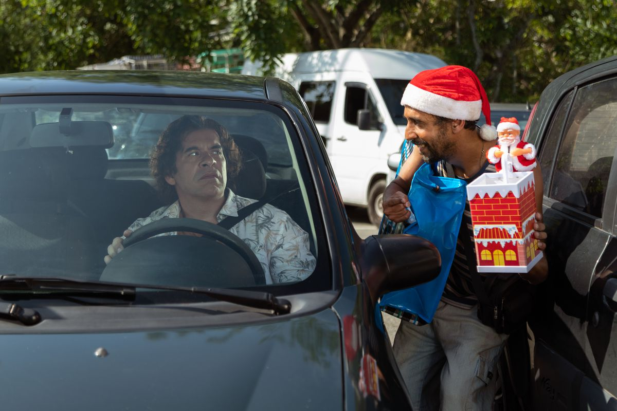 Leandro Hassum sits in his car looking alarmed as someone in a Santa hat confront him