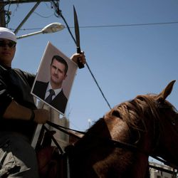 Druze man rides a horse while holding a knife and a photograph of Syrian President Bashar Assad during Syria's Independence Day in the village of Majdal Shams in the Golan Heights, near the border with Syria and Israel, Tuesday, April 17, 2012.