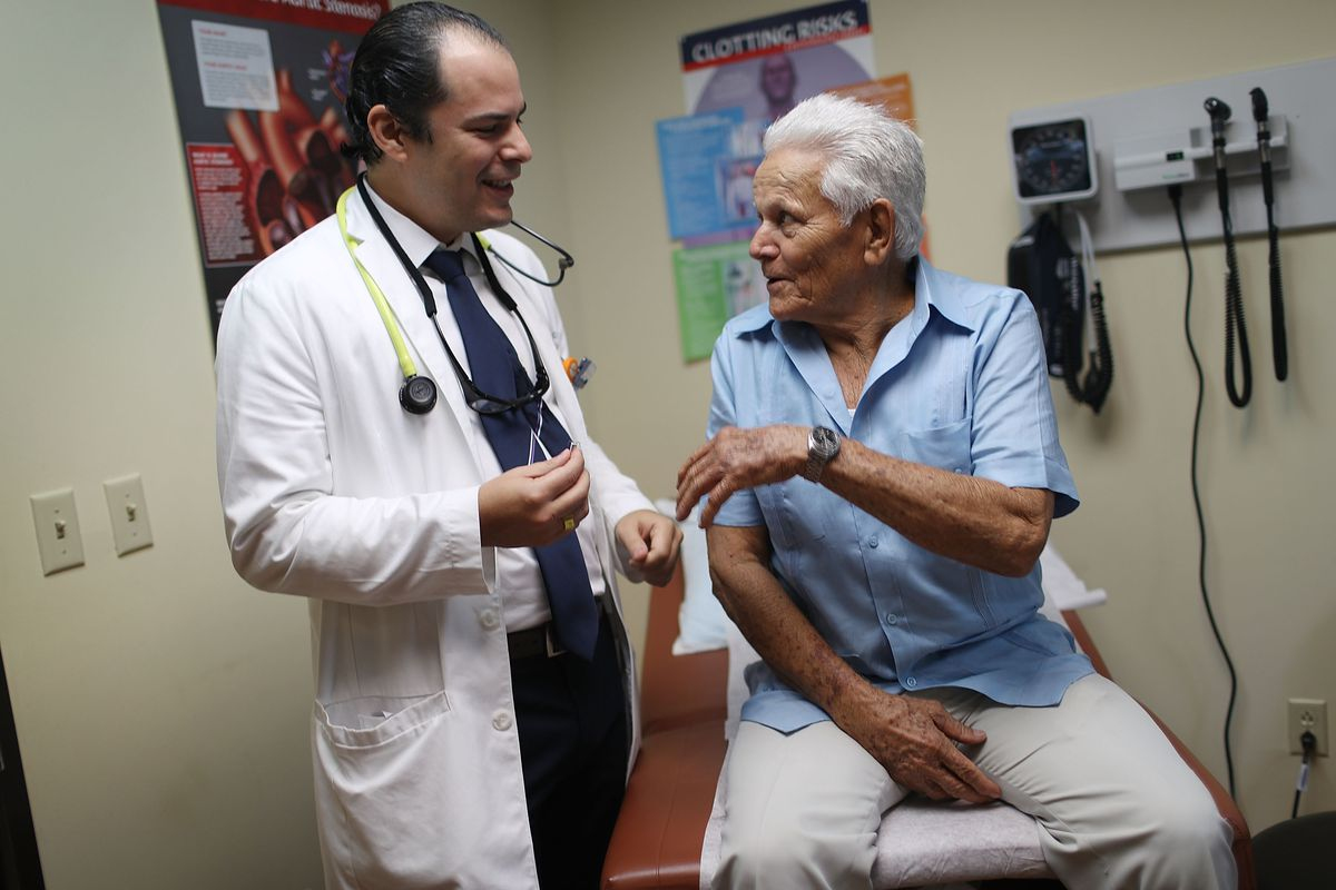 A doctor in a white coat talks to an older patient