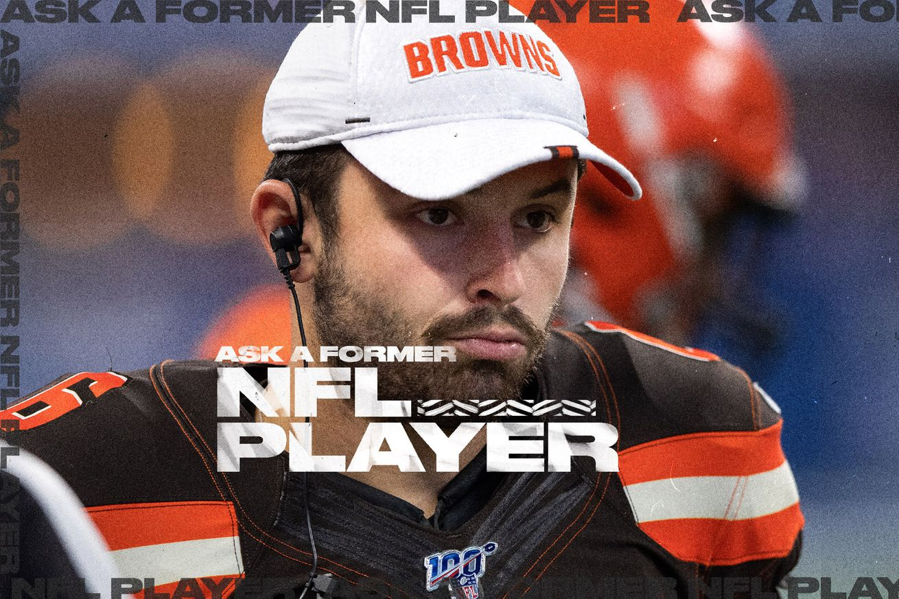QB Baker Mayfield looks in the distance, wearing a Browns hat and earbuds