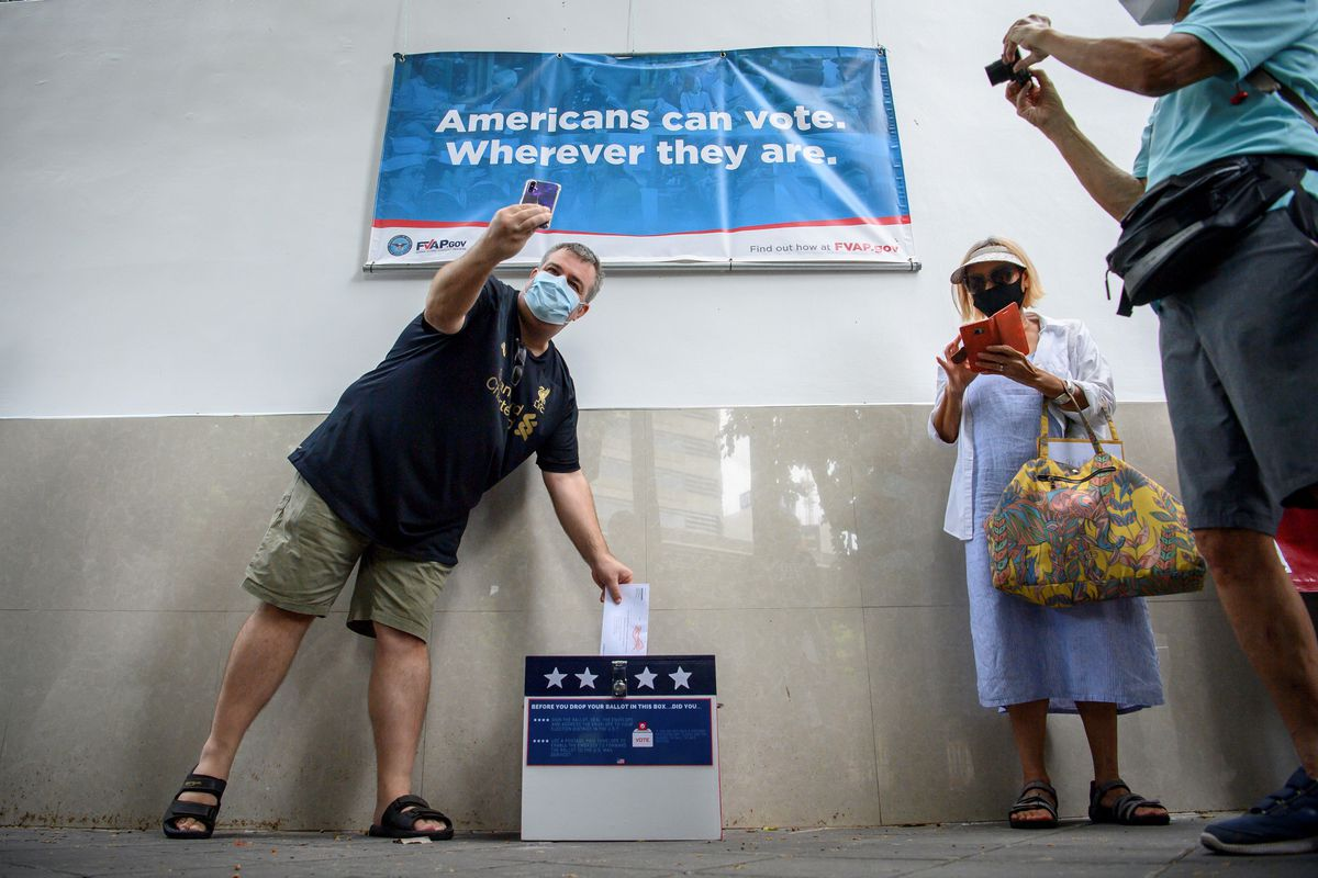 A voter wearing a face mask takes a selfie as he drops a ballot for the 2020 US presidential election in a postbox in Thailand