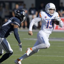 Boise State quarterback Hank Bachmeier (19) runs with the ball as Utah State safety Hunter Reynolds (27) defends during the first half of an NCAA college football game Saturday, Sept. 25, 2021, in Logan, Utah.